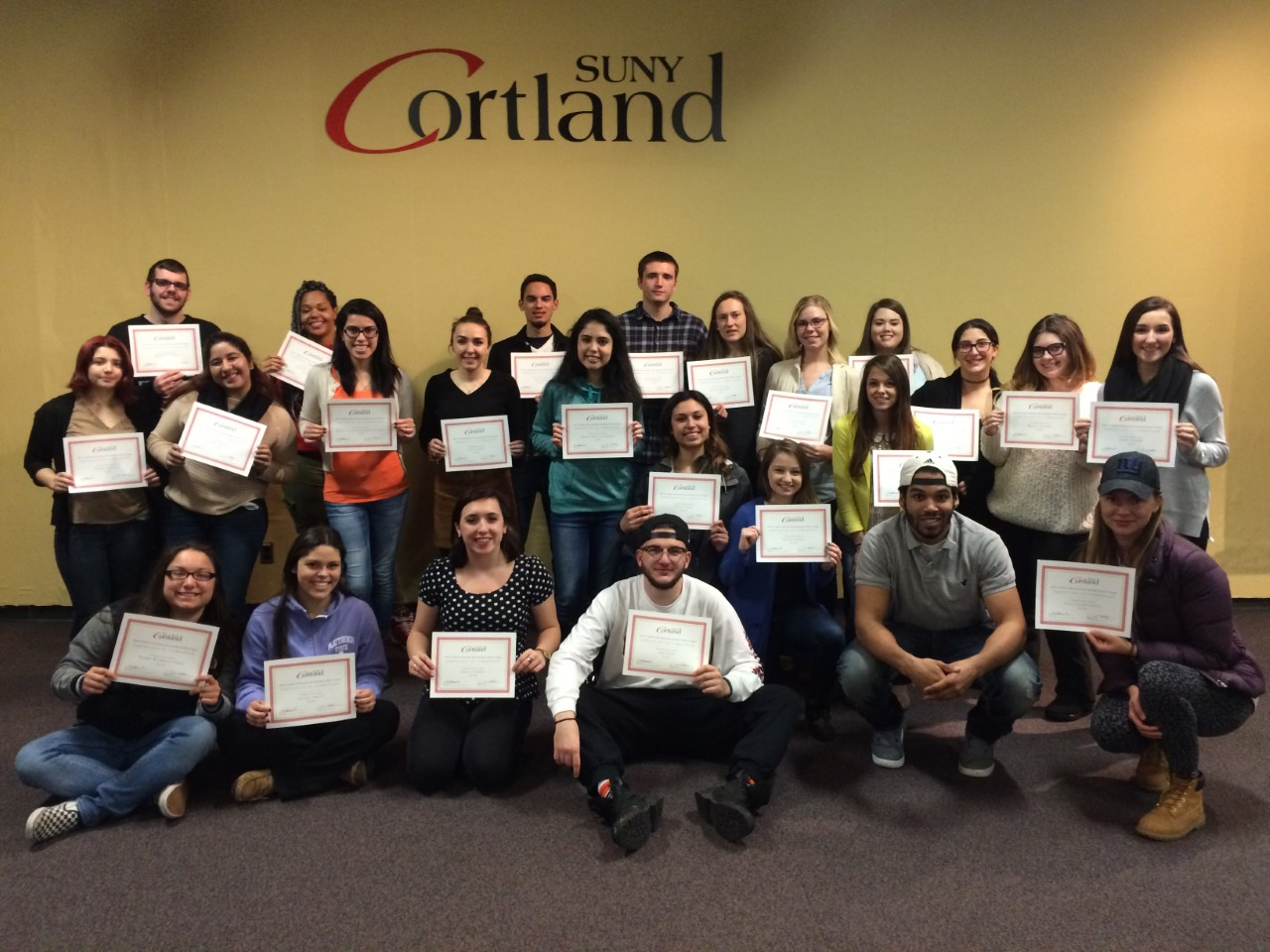 Students hold up certificates for completing Leadership Series