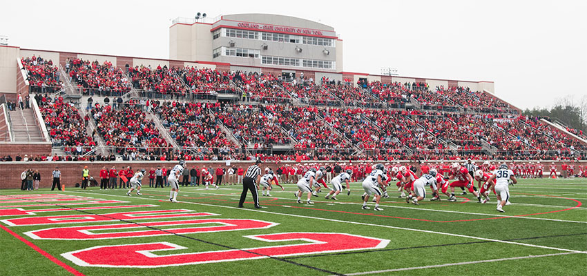The Cortland Football team lines up against the Ithaca Bombers near the endzone at the line of scrimage, with bleachers in the background filled with fans dressed in red.
