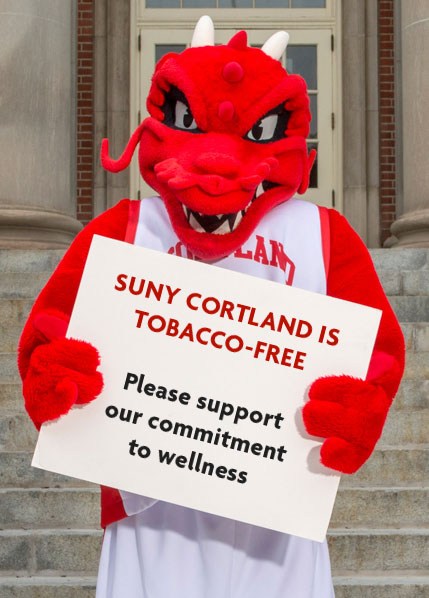 "Blaze holds a sign saying ""SUNY Cortland is tobacco-free. Please support our commitment to wellness."""