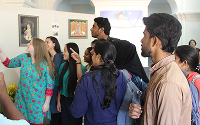classmates in India browse paintings created by SUNY Cortland students