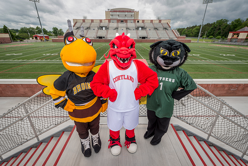 Blaze stands alongside the SUNY Broome and TC3 mascots in front of Red Field