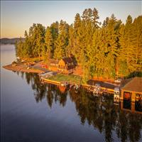Sunset on evergreen trees and cabin next to lake