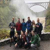 people smiling for picture with waterfall and bridge in background