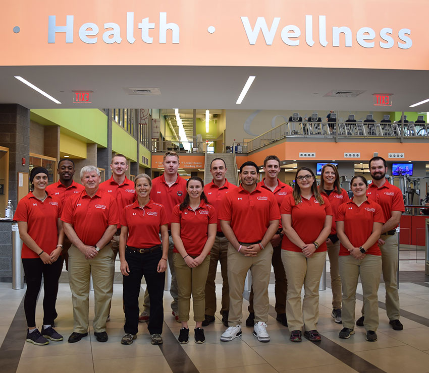 Recreational Sports staff pose together inside the entrance to the Student Life Center