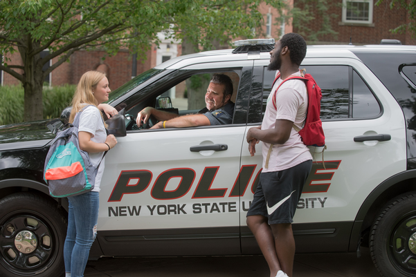 Officer Dalton in patrol vehicle 1702 speaking with two students outside
