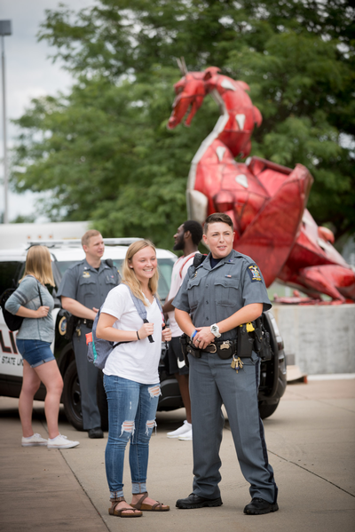 Officer Salisbury and Officer Brooks speaking with three students in front of the red dragon statue