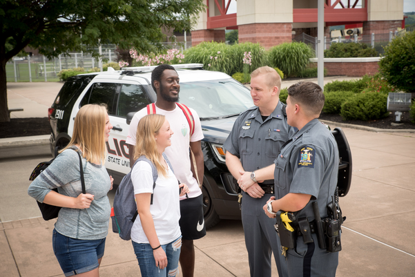 Officers Brooks and Salisbury speaking with three students outside